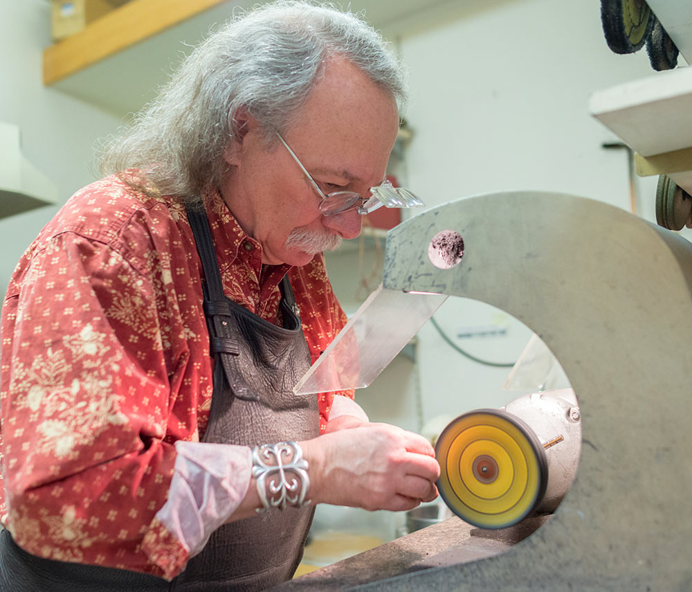 Mark Howard, Goldsmith polishing a piece of jewelry at his design studio in Santa Fe, NM