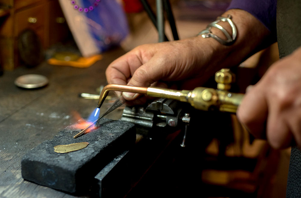 Close-up of Mark Howard working on a piece of custom jewelry in his design studio in Santa Fe